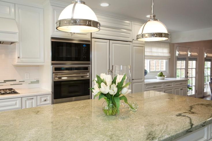 The kitchen gets some of its pizazz from high-end appliances, contemporary pendant fixtures and a green marble countertop. Set against a backdrop of crisp white cabinetry, the beauty of the design is in full focus.