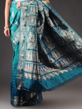 Teal Silk Zari Handwoven Baluchari SareeThis exquisite handwoven silk saree is a Baluchari textile with elaborate depictions of mythological scenes on the pallu and a rich silken texture throughout. Baluchari textiles are characterised by a beautiful pallu, which has a large panel in the centre with zari motifs running all around it. The Ambi or stylised paisley motifs are further worked into the design with fine colours that are akin to a painting.