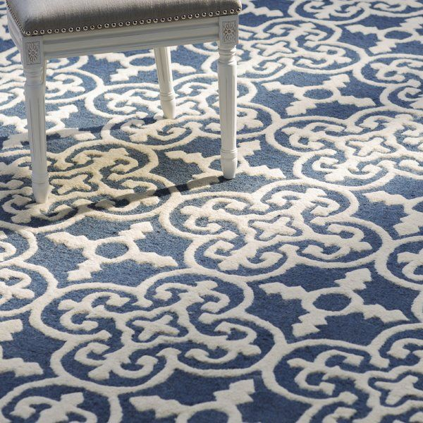 Indulge in traditional style and elevate your home with this beautiful Blue Navy/Ivory Area Rug. Made in India using 100 percent wool pile, this artfully hand tufted rug features plush and loop textures for cozy appeal and dimension, while the blue and white hued geometric, trellis motif is an eye-catcher and great way to create a stylish foundation and focal point in any room. Choose either a round or rectangular shape, and then roll it out on a light, white or gray washed wood paneled ...