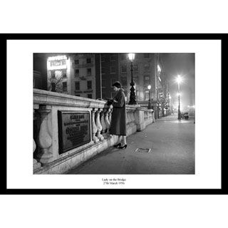27th March 1956, O'Connell Bridge, Dublin. A well-dressed young lady checks the evening paper while waiting for…..