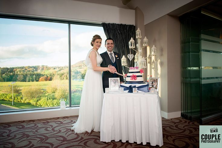 The Bride & Groom cut their cake with the beautiful Sligo view in the background. Wedding at Castle Dargan Hotel Photographed by Couple Photography. Ireland.