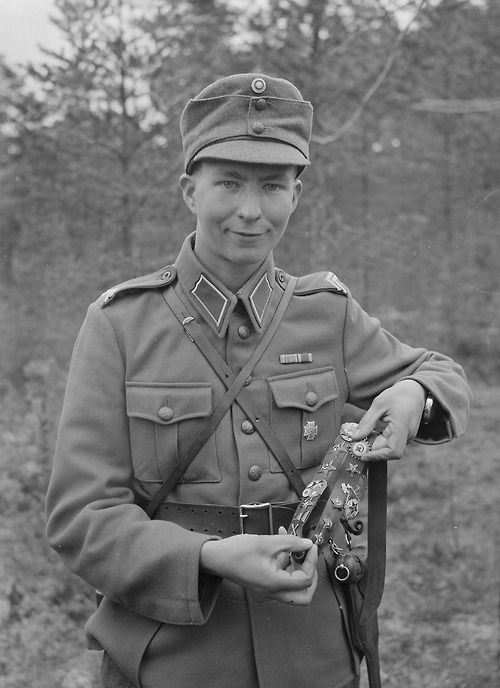 Knight of the Mannerheim Cross, Corporal Vehviläinen proudly displays his war trophies. Pyhäjärvi, 1941.09.28 Continuation War