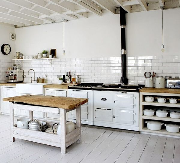 All white kitchen. Beautiful white Aga mixing traditional cooking with a faster dual fuel module. Open shelves for displaying crisp white ceramics. Aged timber tops soften the whole look of the kitchen and keeps it from looking too cold or clinical.