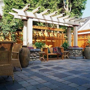 bhg.com  Craftsman-style fence screens a small backyard patio from its neighbors and creates a warm backdrop for outdoor living. A shallow post-and-beam pergola raised on massive river-rock bases.