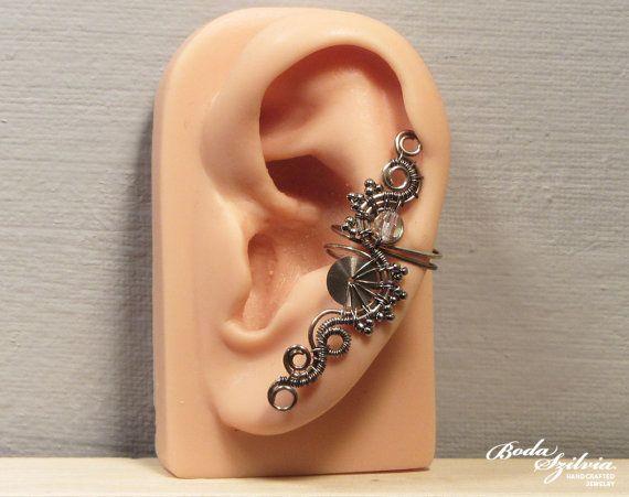 Diseño de edición limitada. Ajustables del alambre envuelven steampunk brazalete de oído, no requiere de perforación.  Está hecho de alambre de plata libre de níquel, rocallas de color plata, una perla de cristal de swarovski AB transparente y una rueda de reloj de acero inoxidable. Envejecido y pulido cuidadosamente.  Usted puede usarlo en la oreja izquierda o derecha.  Hecho para la orden. Necesitaré 1-5 días para hacer el brazalete de su oído. Tenga en cuenta que cada uno está hecho 100%…