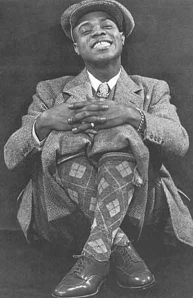 American jazz singer and trumpeter Louis Armstrong (1901 - 1971) wearing a woolen suit, cap and argyle socks in London during his first tour of Europe, 1933. Photo by Frank Driggs.