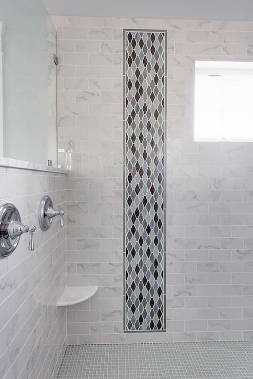 oversize walkin shower with marble subway tiled surround accented with a slim vertical panel of blue and gray arabesque tile with corner shower ledge to