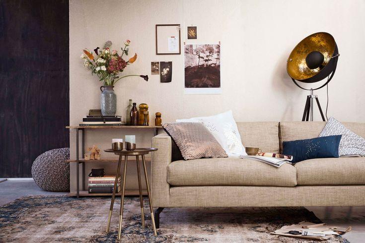 Woonkamer met vloerlamp en bruine meubels en accessoires | Living room with…