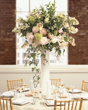 Pink peonies, pale green viburnum, sweet olive, clematis and jasmine vines, and hydrangea overflow from tall milky-glass vases.