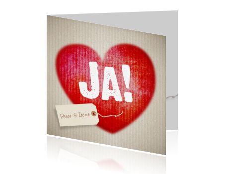 Trendy uitnodiging huwelijksfeest kaart. Groot rood hart met daarin de tekst JA! Op een stoere achtergrond van karton. Dit wordt een bruiloft om nooit te vergeten, nodig al jullie vrienden en familie uit om dit samen met jullie te vieren met deze trouwkaart uitnodiging voor jullie huwelijk. Originele kaart van Luckz.