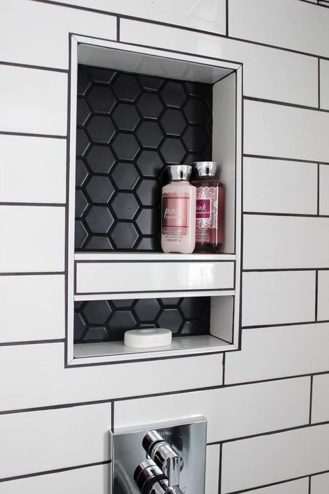 A beautiful modern bathroom renovation with chrome and matte black faucets, sleek modern fixtures and natural wood accents. Beautiful transformation! Subway tile with black grout, wood grain tile, black hexagon tile, turkish towels, natural wood accents, industrial chic, built-in natural wood shelving, floor to ceiling shower glass, niche