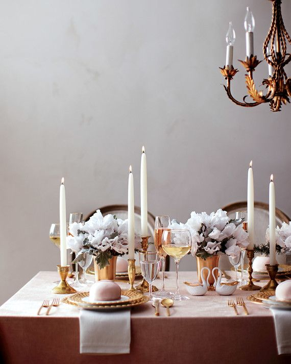 This inviting tablescape strikes the perfect balance between elegant and cozy. Pull it off with simple centerpieces that use just one or two types of blossoms, a pared-down palette of rosy white and antique gold, and lots of ultra-flattering candlelight. Here, densely clustered stems of white cyclamen and dusty miller are anchored in brass vases and placed among slender taper candles in varying holders.