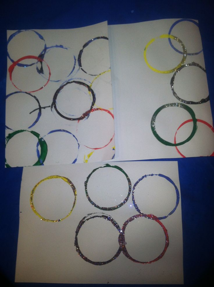 Camp Olympics Theme Day Art activity. This was done using plastic cups set out on plates of tempera paint in the colors of the Olympic Rings. Kids enjoyed stamping the ring onto the paper. Kids generated a list of olympic sports at circle time. We talked about the meaning of the rings and the colors and then we added glitter. Glitter makes everything better!!!
