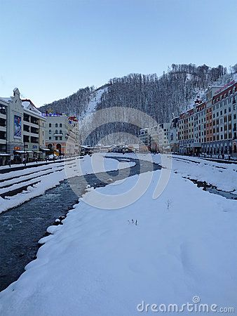 Snowy stream, hotel buildings and parking on the waterfront, mountains with ski slopes, winter in Krasnaya Polyana, Russia