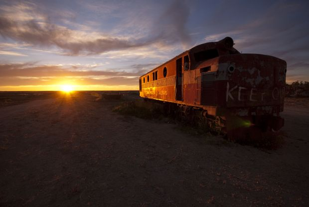 """THIS RELIC OF THE Ghan, the train that runs from Adelaide to Darwin, is captured in this week's reader photo sent in by Ken Sedgmen, from Coffs Harbour in NSW. """"This image was taken at sunset at Marree in outback South Australia,"""" says Ken. """"[It] captures the setting sun lighting up one of the retired Ghan engines sitting on a disused siding."""""""