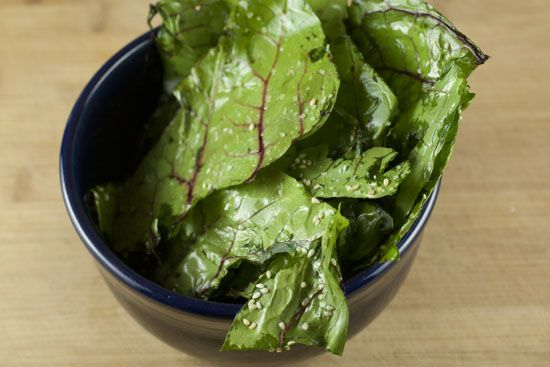Baked swiss chard leaves with sesame seeds and olive oil. If done correctly they turn into cool little crispy leaves!