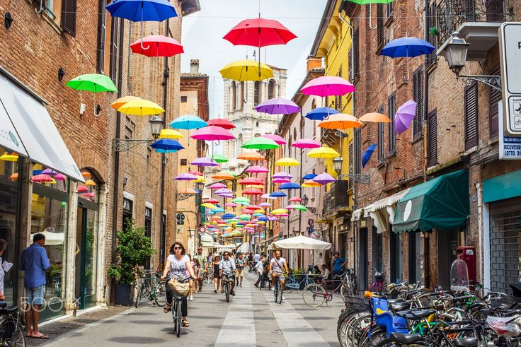 Via Giuseppe Mazzini of Ferrara. Emilia-Romagna. Italy. - Ferrara, Italy - July 21, 2016. Cyclists crossing Via Giuseppe Mazzini of Ferrara covered with colored umbrellas and tower of San Giorgio cathedral in background. Emilia-Romagna. Italy.