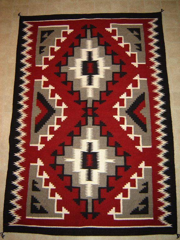"A Ganado style rug.  (Ganado post started by Don Lorenzo Hubbell in 1876. ""Ganado red"" and stair-step diamond as style features.)"