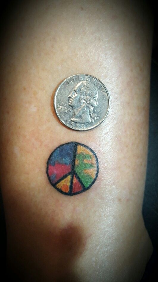 Tiny tie dye peace sign tattoo on ankle