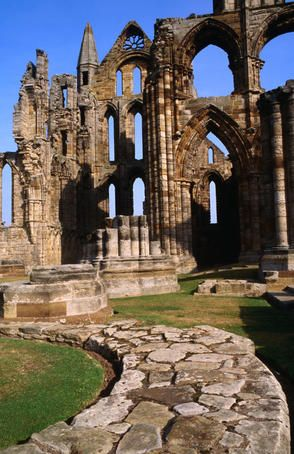 Whitby Abbey is a ruined Benedictine abbey overlooking the North Sea on the East Cliff above Whitby in North Yorkshire, England. It was disestablished during the Dissolution of the Monasteries under the auspices of Henry VIII. It is a Grade I Listed building in the care of English Heritage and its site museum is housed in Cholmley House.
