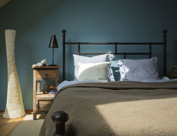 Metal bed from Le Patio against blue grey wall. Bed cover Vivaraise.