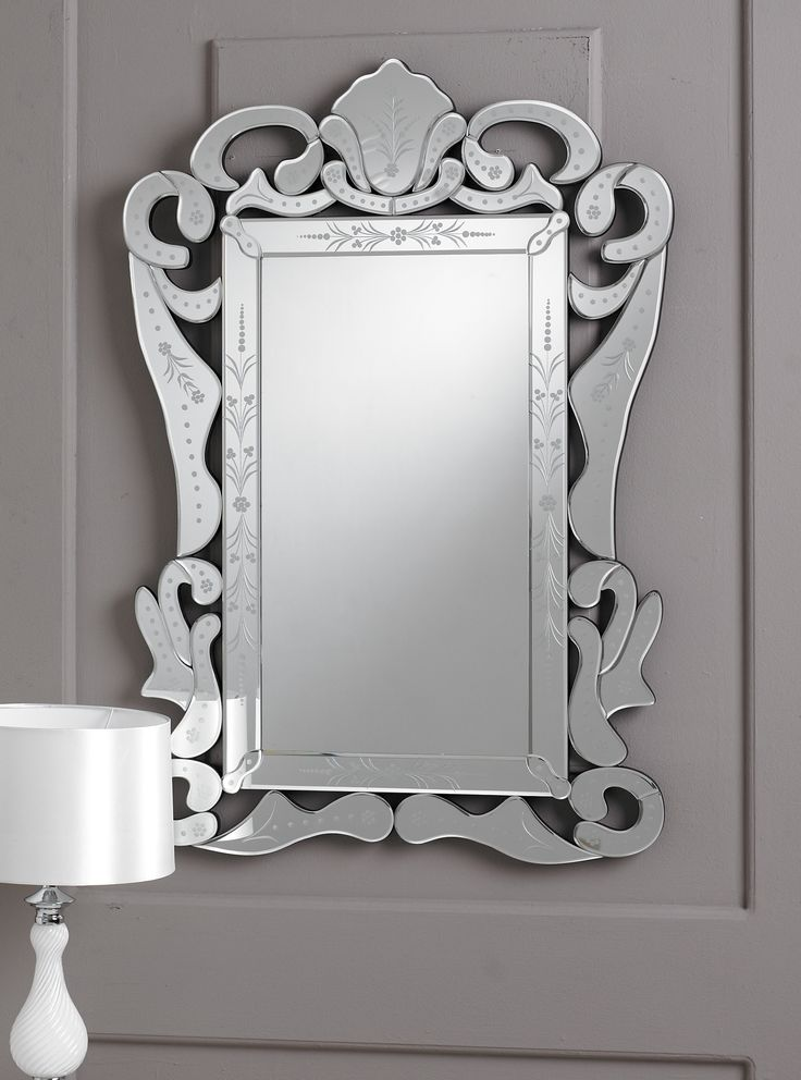 This is a classic Venetian mirror,  featuring the typical looping ornamental decorations around the clear glass border, as well as the intricate detail of the glass etching in the frame.
