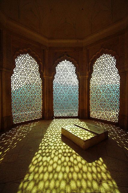 Amber Fort in Jaipur, India.  conservatory is located on the south side of the Amber Fort in Jaipur, India.    The three windows are carved from stone with a repeating geometric pattern