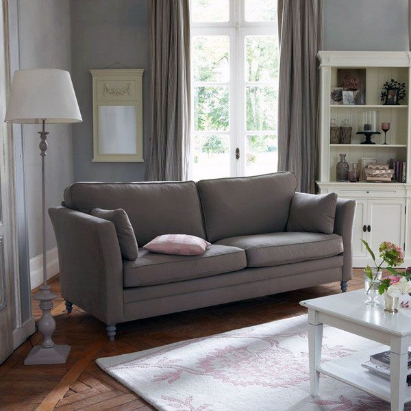 Grey classic sofa with flower cushions combined by laminate flooring, cream fur rug, white table wood, standing lamp, brown curtains, cabinets and shelves