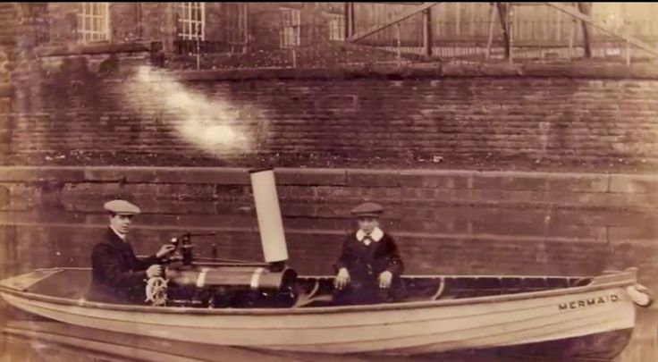 A photograph of father and son Harry and James Smith sailing down the canal in their small steam powered craft the 'Mermaid'. The boat was built by Harry who was a canal boat carpenter. Harry was the husband of Maud smith who had a grocers shop on cow lane. It is believed that the photograph was taken near to to Finsley Warf.