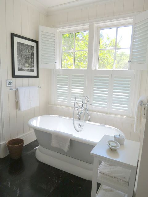 Plantation shutters allow for privacy and sunlight | white soaking tub, plantation shutters