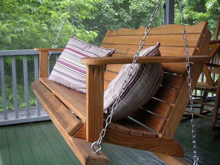 country house porch with wooden hanging chair feat classic pillows