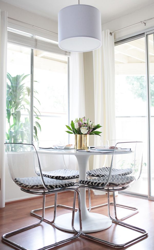 clear chairs that have minimal visual weight and a round table for good traffic flow in a small space