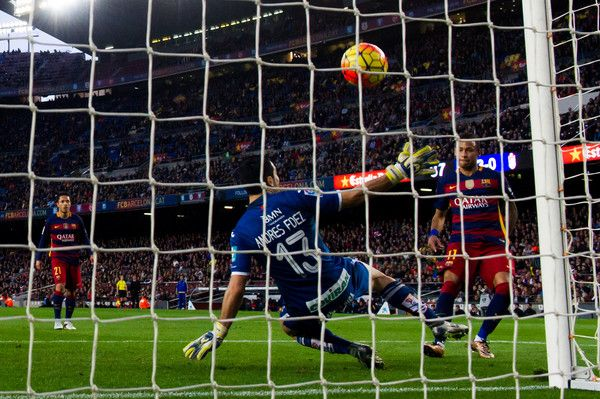 Neymar Santos Jr of FC Barcelona shoots the ball past Andres Fernandez of Granada CF and scores his team's fourth goal during the La Liga match between FC Barcelona and Granada CF at Camp Nou on January 9, 2016 in Barcelona, Catalonia.