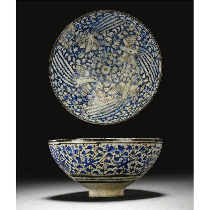 AN ILKHANID SLIP-PAINTED BOWL, PERSIA, CIRCA 1300 of deep rounded 'lotus bowl' form, decorated in underglaze blue and black outlines with a chinoiserie design of phoenix circling around a central pearl motif reserved on a ground of lotus flowers and foliage, the back with vegetal and floral motifs 20.5cm. diam.