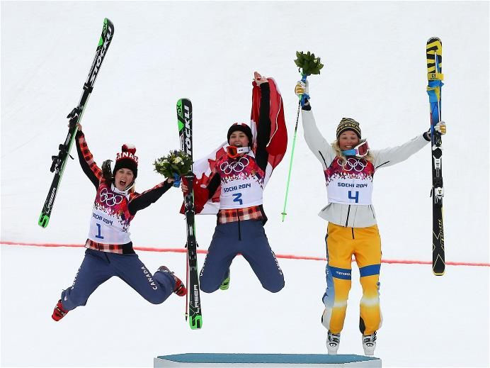 Marielle Thompson (C) of Canada celebrates winning the gold medal with silver medalist Kelsey Serwa (L) of Canada and bronze medalist Anna Holmlund of Sweden during the flower ceremony in the Freestyle Skiing Womens' Ski Cross Final #Sochi #Olympics 2014