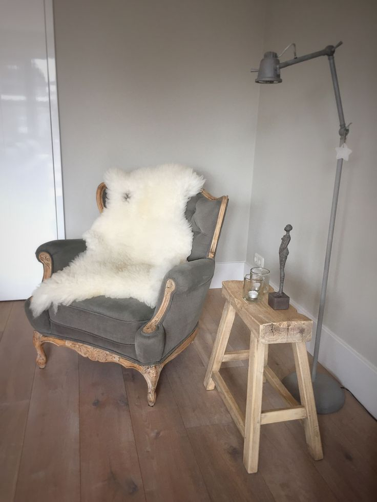 Geef een oud Lodewijkstoeltje een stoere look met een grijze linnen bekleding en kaalgeschuurd hout. Een wollig schapenvachtje eroverheen maakt het geheel af. Naast het stoeltje een oud zadelkrukje met een lief vrouwenbeeldje. Een blikvanger is ook de (een tikkeltje industriële) lamp van Frezoli.