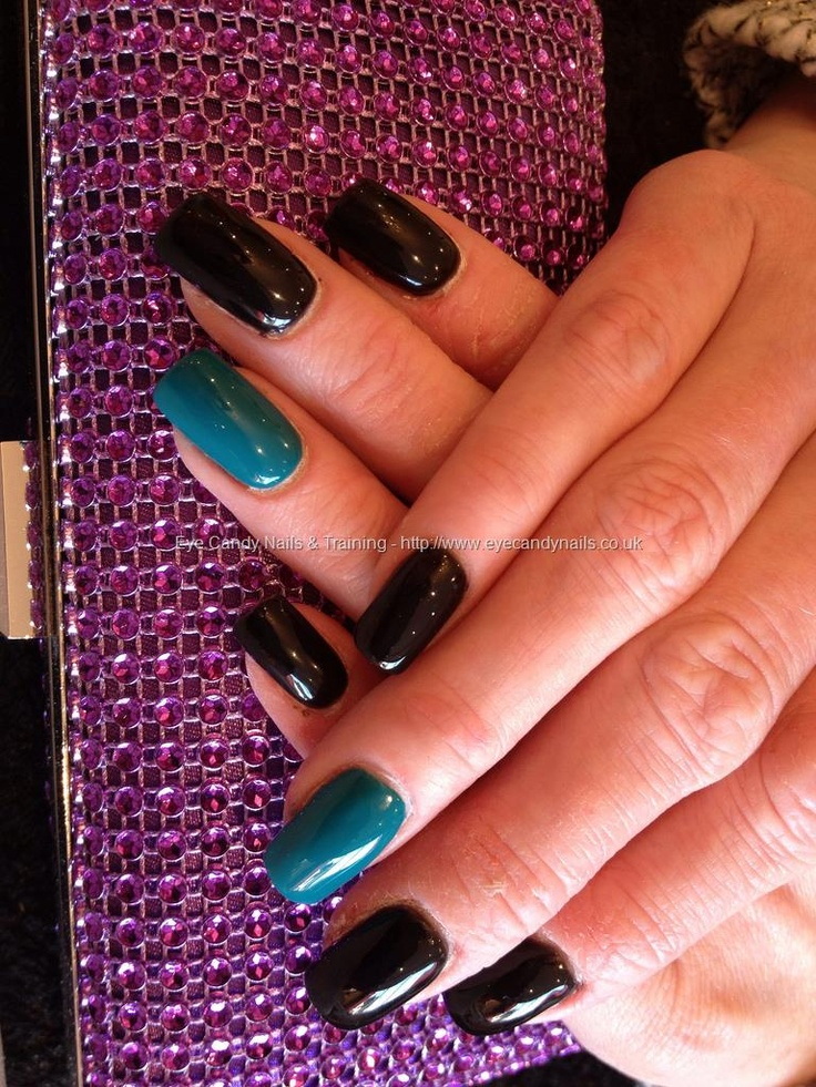Acrylic nails with black gel polish and green gel polish on ring finger