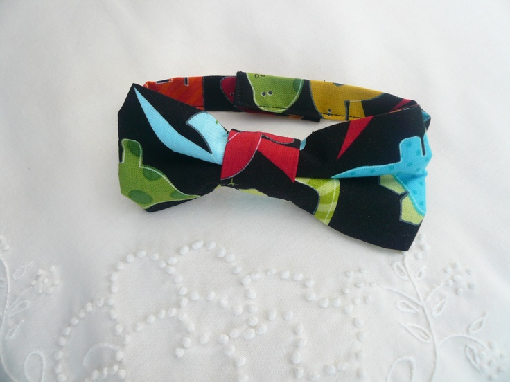 This child size Dinosaur bow tie is sure to add spunk to your little man's outfit.  Some say wearing a bow tie brings out the inner genius?????    This dinosaur bow tie has a neck strap it can also  attached to a metal alligator clip that grips firmly.  It measures approximately 11cms across and 5cms wide.  For more  designs see http://www.facebook.com/MamasLoveChildrensClothingAndAccessories