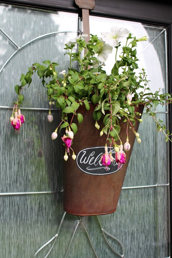 Love this idea to use a bucket with fresh flowers for the front door instead of a wreath! Love using Chalk Ink to write Welcome.