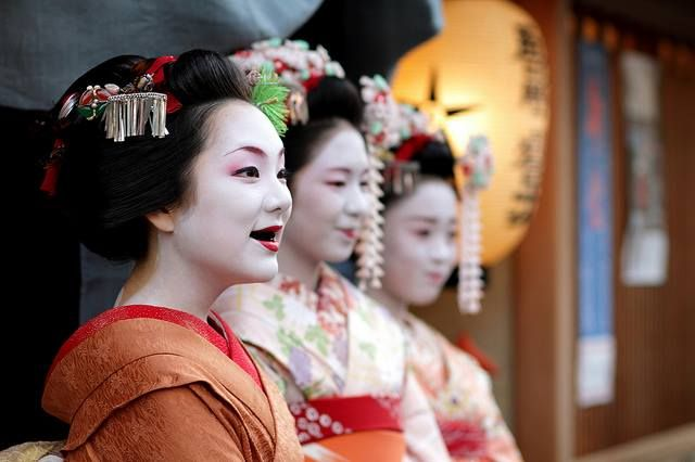 The maiko on the far left is a good example of the practice of ohaguro (teeth blackening) which was common during the heian era.