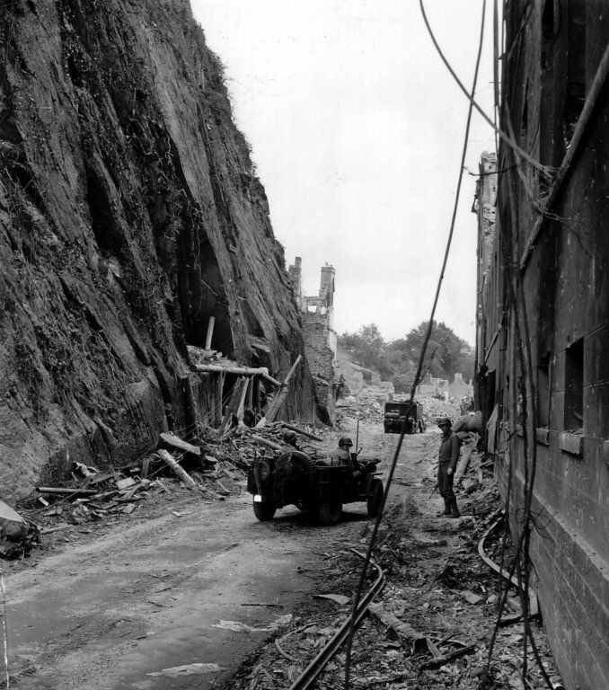 St. Lo, France, July 1944: Two GIs in a Jeep pass outside a German military hospital that was built inside the rock cliff on the left. The hospital was halfway finished when US forces took St Lo from the Germans. During the fighting, the Germans allowed wounded local civilians to shelter in this underground facility during the initial bombardment of June 6, 1944.