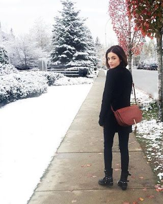Lucy Hale wearing black coat, boots and Vera Bradley saddle bag on snowy day in Canada. Fashionable winter outfit!