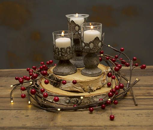 Lighted led branches with red berries are curled around natural birch tree slice risers - Appealing christmas led candles for christmas decorations ...