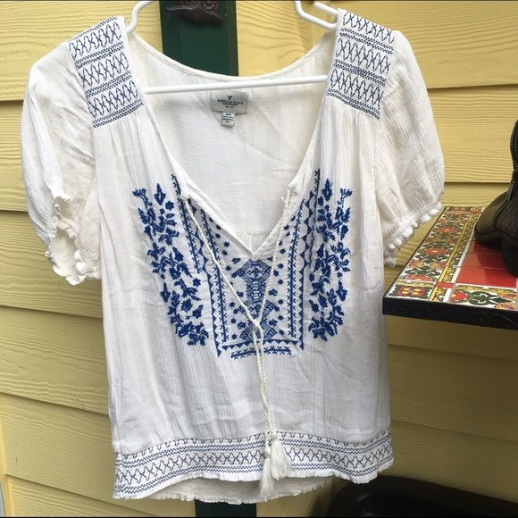 American Eagle Smock Crop Top A gauzy, blue & white embroidered top with ties . It has a little bit of wear near the top of the ties but other than that it's in perfect condition! Hard to let this go, but I need the right now. American Eagle Outfitters Tops Blouses