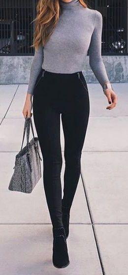 Ella lleva una camisa gris y un bulso blanco y negro. Ella lleva pantalones negro y una botas negro. Una camisa y un pantalones cuesta trenta dolares y un bulso y botas cuesta novento dolares.