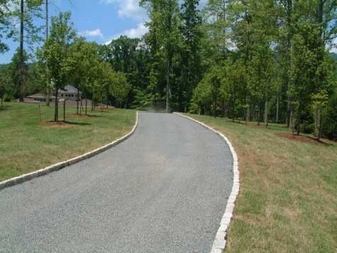 Tar and chip driveway edged with Belgian Block curbing. What is tar and chip? First, it's a beautiful, rustic, inexpensive choice for a driveway paving! Find out more.