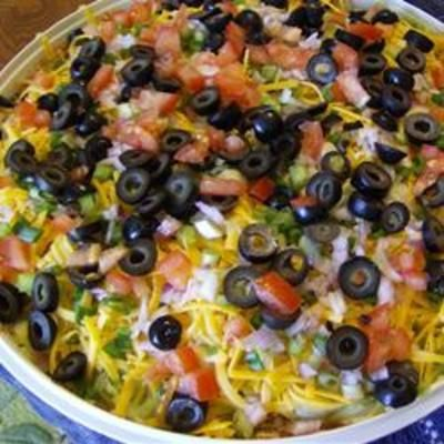 Mexican Layered Dip  Ingredients 1 (16 ounce) can refried beans 1 (1.25 ounce) package taco seasoning mix 1 large tomato, seeded and chopped 1 cup guacamole 1 cup sour cream, room temperature 1 cup shredded sharp Cheddar cheese 1/2 cup chopped green onions 1/4 cup chopped black olives Directions: Spread refried beans in the bottom of a (1-quart) shallow edged serving dish (you can use a transparent dish if you'd like). Sprinkle the seasoning packet over the beans. Layer the diced tomatoes over t