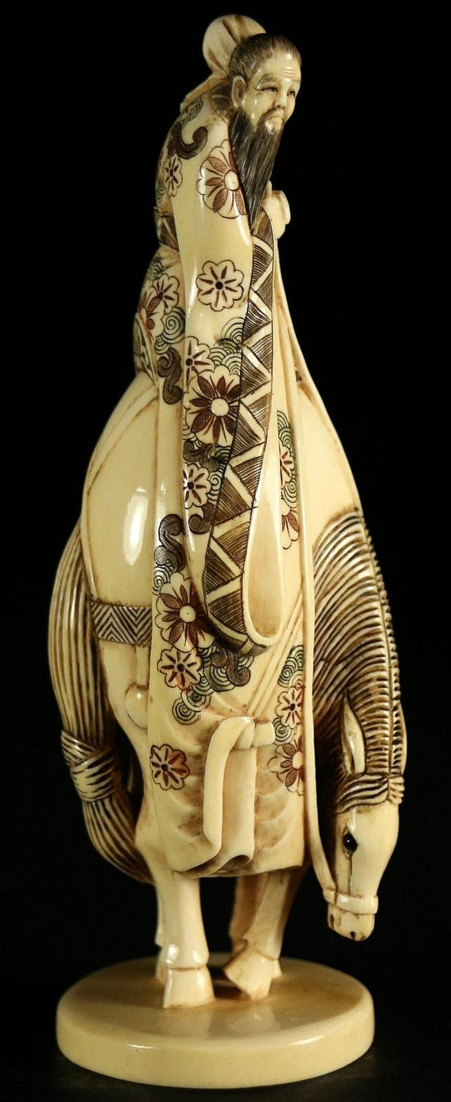 Ivory, Wise man on Horse, Japanese C. 1920 -  Sculpture of a man on horseback, this is a well detailed carving of a man in elaborately embroidered robes riding a horse. The horse holds his neck and head down low. Signature is on the bottom of the piece