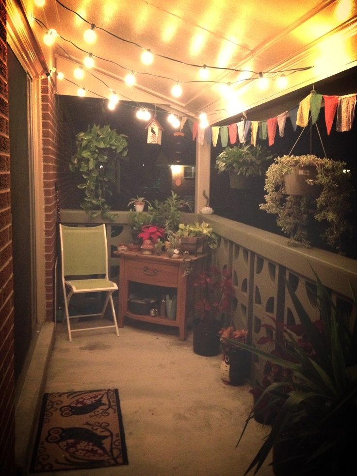 My balcony! String lights, old nightstand, prayer flags and plants.