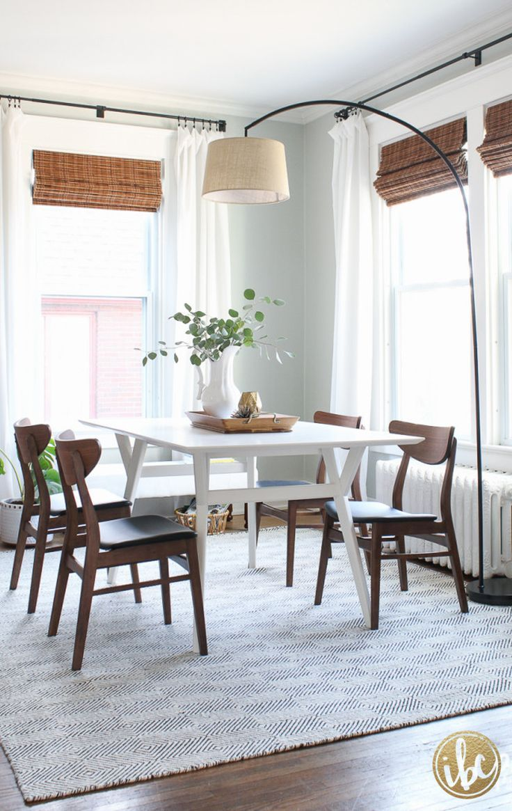 a lovely, simple dining room with pale walls, white curtains, black curtain hardware hung above the window, bamboo shades, white table, wood chairs, green plants, simple decor | Best of 2016: Interiors - Inspired by Charm